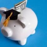 Piggy bank with a graduation cap with dollar bill