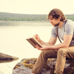 55633056 - young man reading book outdoor with scandinavian lake on background education and lifestyle travel concept