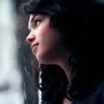 Beautiful girl looks out of the window. On its lips an easy smile, and behind a window a rain.