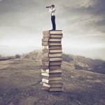 14022415 - young businessman standing on a stack of books and using a telescope
