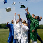 Group of graduates toss their hats into the sky with jubilation. There is a small hint of blur in the motion of the toss.
