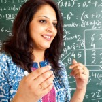 Young Cheerful Indian Mathematics Teacher in a Classroom interacting with the class