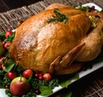 Golden brown, roast turkey garnished with pears, crab apples, cranberries, savory and kale.