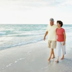 Loving mature man and woman walking at water's edge on a beach