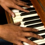 black woman with long exquisite fingers playing an old piano