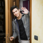 35114849 - smiling young man getting out of door waving at the camera with a friendly cheerful smile as he peers around the edge of a wooden door